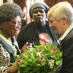 Nokuthula's mother receiving a bunch of flowers from a member of the CMVO Military Veterans Organisation